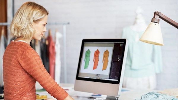Lady looking at dress designs on iMac