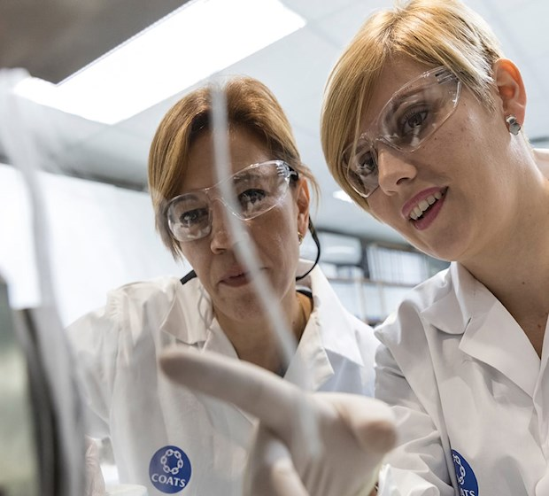 Two lab technicians examining threads