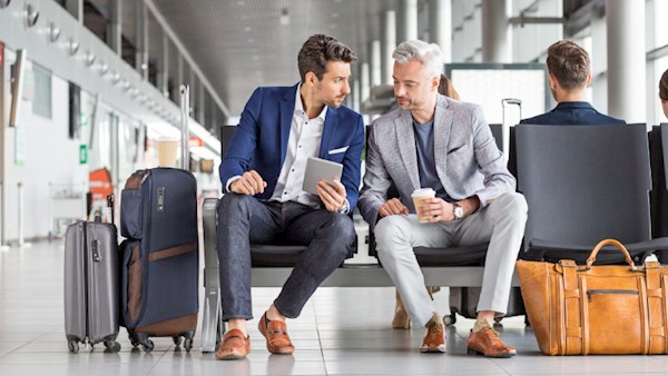 Two men at airport waiting room wearing suits